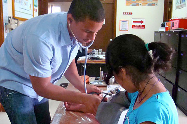 Photo: A male student taking vitals in Oaxaca, Mexico.